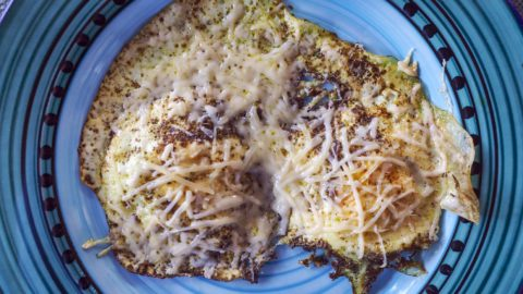 green pesto fried eggs with Parmesan cheese on a blue plate