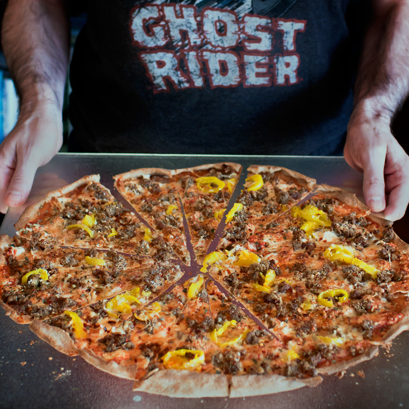 man in a ghost rider shirt holding tray of homemade pizza