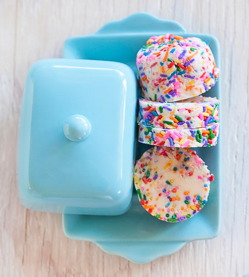 rainbow sprinkles compound butter log cut into rounds on a blue butter dish